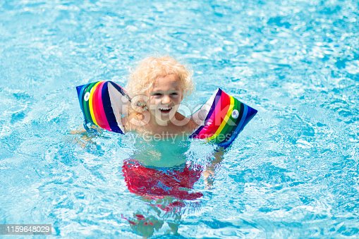 1159904048istockphoto Child in swimming pool. Kid with float armbands. 1159648029