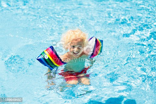 1159904048istockphoto Child in swimming pool. Kid with float armbands. 1159649452