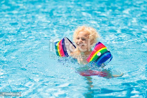 1159904048istockphoto Child in swimming pool. Kid with float armbands. 1159903190