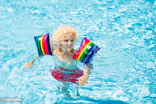 istock Child in swimming pool. Kid with float armbands. 1159905698