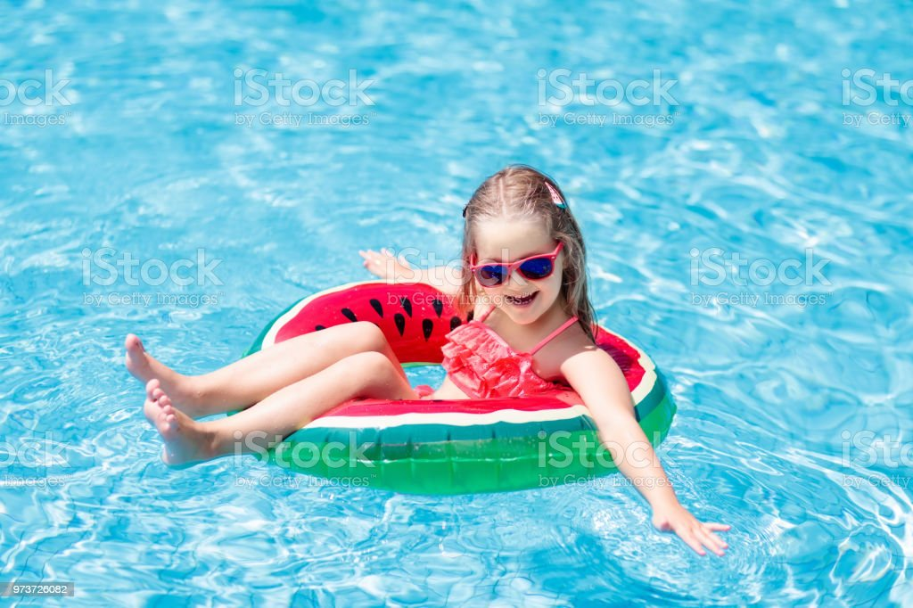 Child in swimming pool. Kids swim. Water play. stock photo