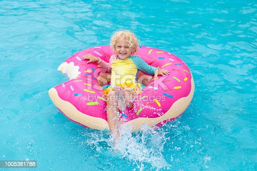 1159904048istockphoto Child in swimming pool on donut float 1005381788