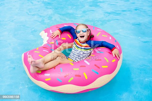 1159904048istockphoto Child in swimming pool on donut float 990586158