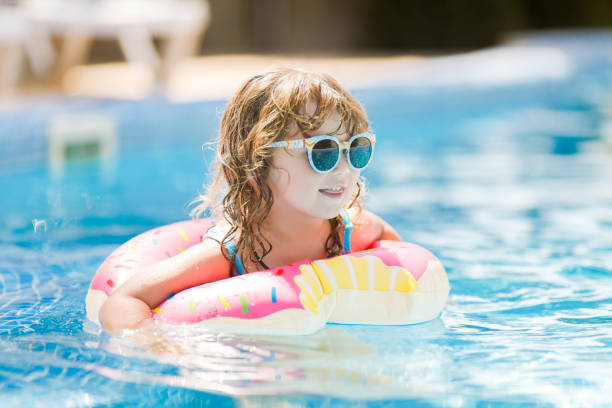 Child in swimming pool on funny inflatable donut float ring, learning how to swim. stock photo