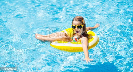 1159904048istockphoto Child in swimming pool on ring toy. Kids swim. 1159903320