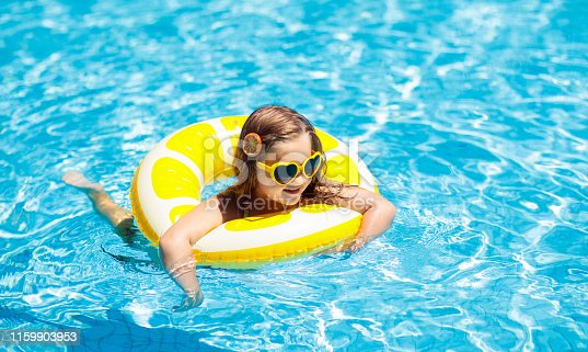 1159904048istockphoto Child in swimming pool on ring toy. Kids swim. 1159903953