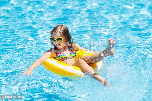 1159904048istockphoto Child in swimming pool on ring toy. Kids swim. 1159904012