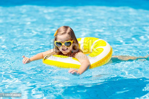1159904048istockphoto Child in swimming pool on ring toy. Kids swim. 1159904040