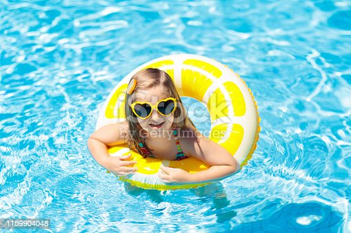 istock Child in swimming pool on ring toy. Kids swim. 1159904048