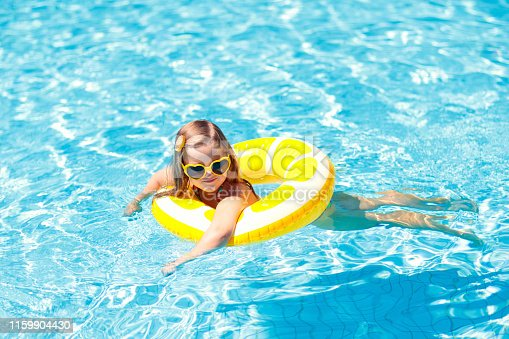 1159904048istockphoto Child in swimming pool on ring toy. Kids swim. 1159904430