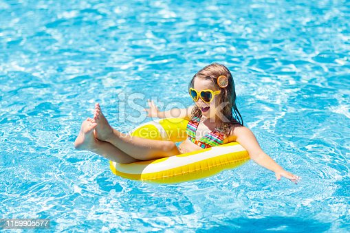 1159904048istockphoto Child in swimming pool on ring toy. Kids swim. 1159905577
