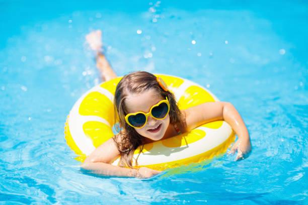 Kind im Schwimmbad auf Ringspielzeug. Kinder schwimmen. – Foto