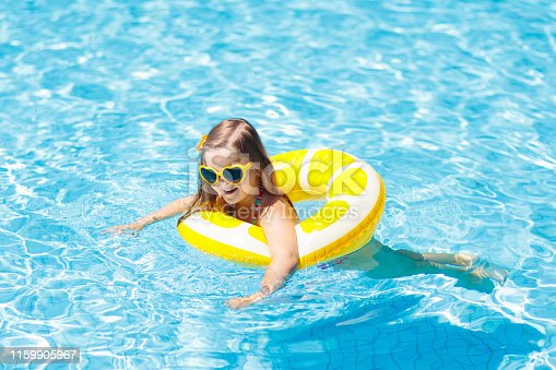 1159904048istockphoto Child in swimming pool on ring toy. Kids swim. 1159905967