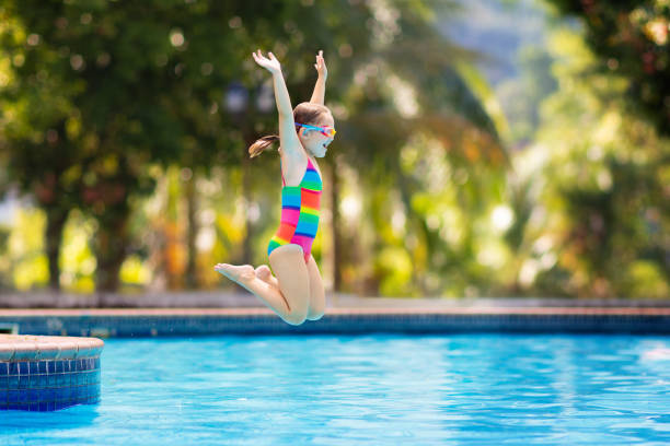 Child in swimming pool on toy ring. Kids swim. Child jumping and diving in swimming pool. Kids swim, jump and dive. Colorful rainbow swim wear for young kids. Little girl having fun on family summer vacation in tropical resort. Beach and water fun swimming pool stock pictures, royalty-free photos & images