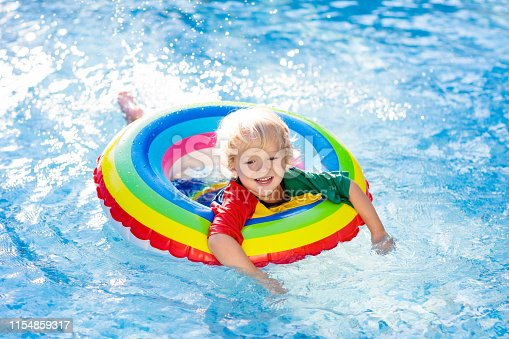 1159904048istockphoto Child in swimming pool on toy ring. Kids swim. 1154859317