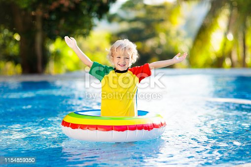 1159904048istockphoto Child in swimming pool on toy ring. Kids swim. 1154859350
