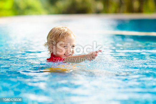 istock Child in swimming pool. Summer vacation with kids. 1080429336