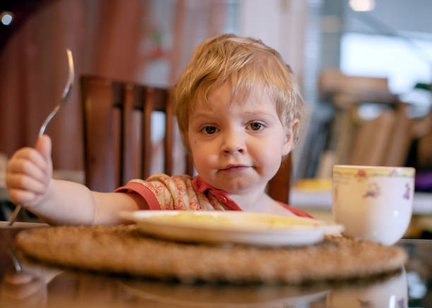 child in the kitchen eating sausage and mashed potatoes child in the kitchen eating sausage and mashed potatoes hungry stock pictures, royalty-free photos & images