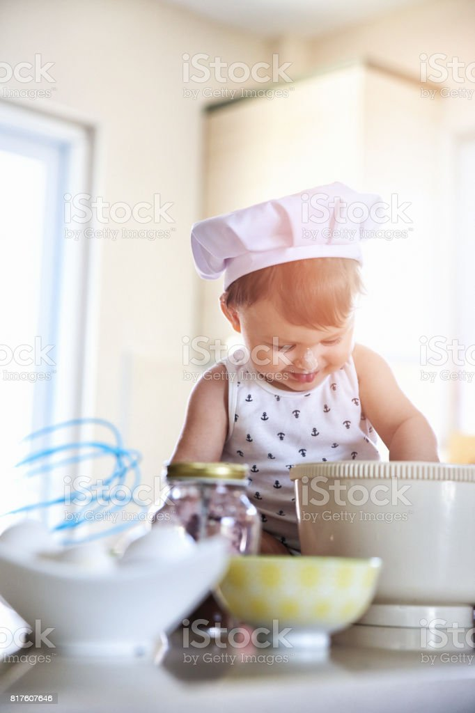 Child in the kitchen preparing a meal stock photo