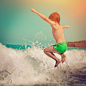 Happy little boy playing in waves