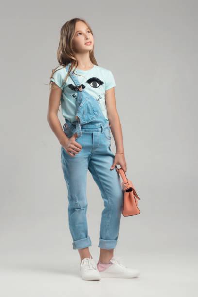 kind in das studio posieren in modische kleidung - jeans overall stock-fotos und bilder