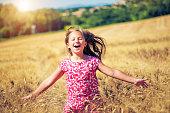 Little girl walking in the wheat field