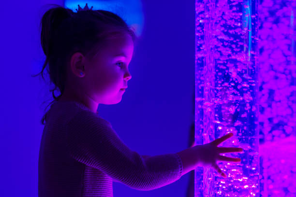 child in therapy sensory stimulating room, snoezelen. child interacting with colored lights bubble tube lamp during therapy session. - percezione sensoriale foto e immagini stock