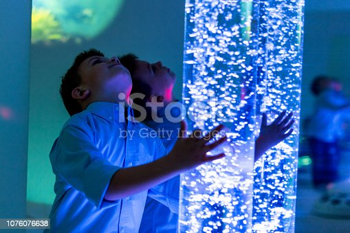 istock Child in therapy sensory stimulating room, snoezelen. Child interacting with colored lights bubble tube lamp during therapy session. 1076076638