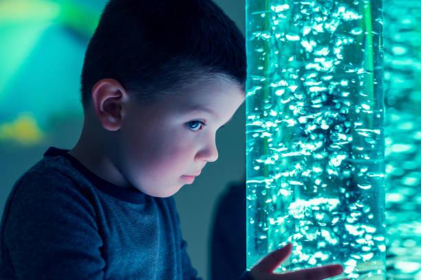 Kind in anregenden Snoezelenraum Therapie, Snoezelen. Kind-Interaktion mit bunten Lichtern Blase Schlauch Lampe während der Therapiesitzung. – Foto