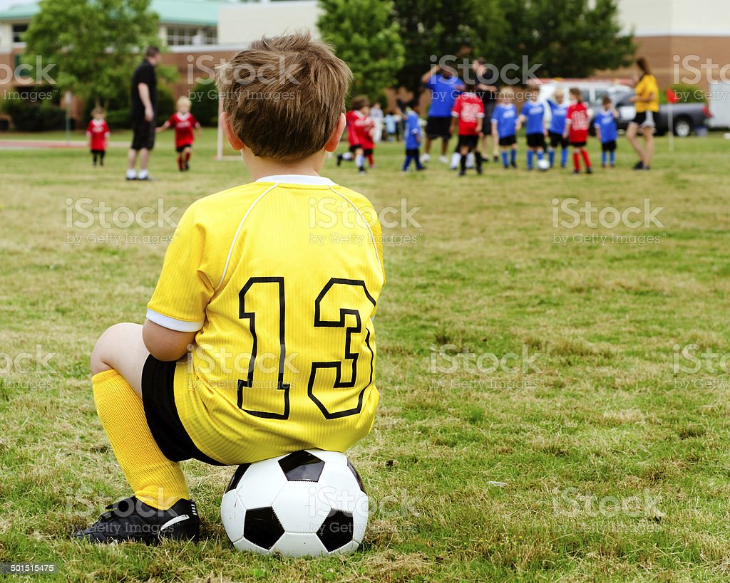 Child in uniform watching organized youth soccer royalty-free stock photo