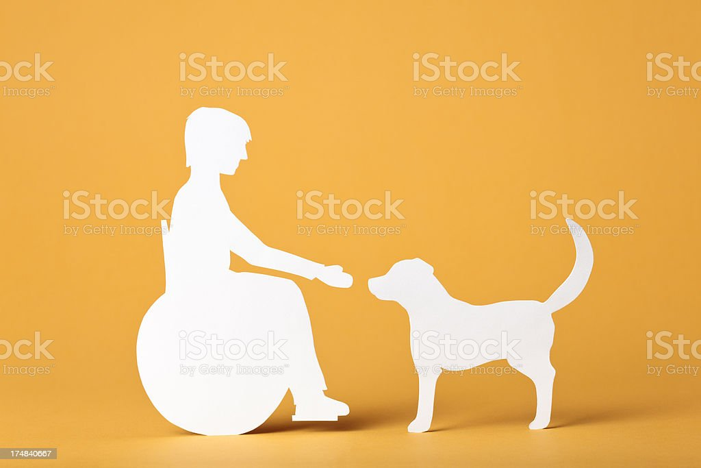 Child in wheelchair interacting with a dog: paper concept royalty-free stock photo