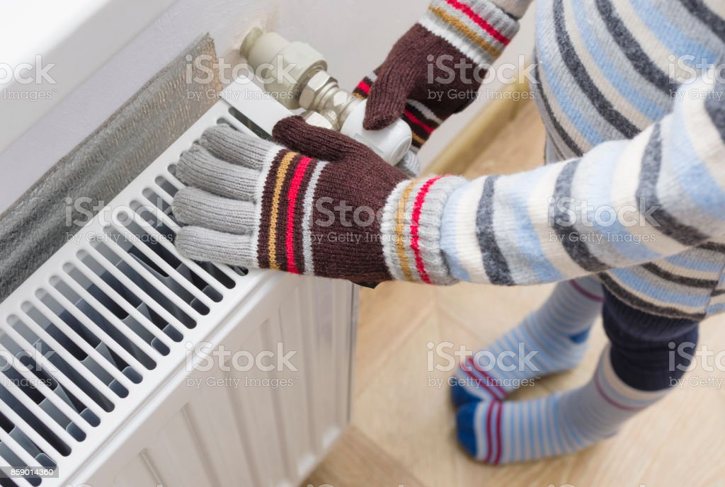 A child in woolen gloves and a sweater warms his hands near the heater. stock photo