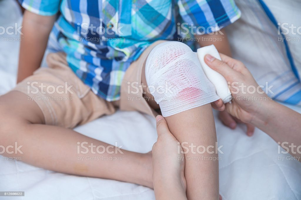 Child injured. Mother bandaging son's knee. stock photo