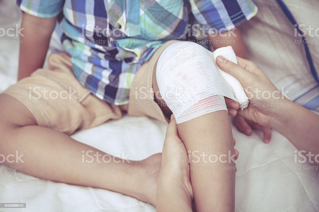 Child injured. Mother bandaging son's knee. Vintage style. stock photo
