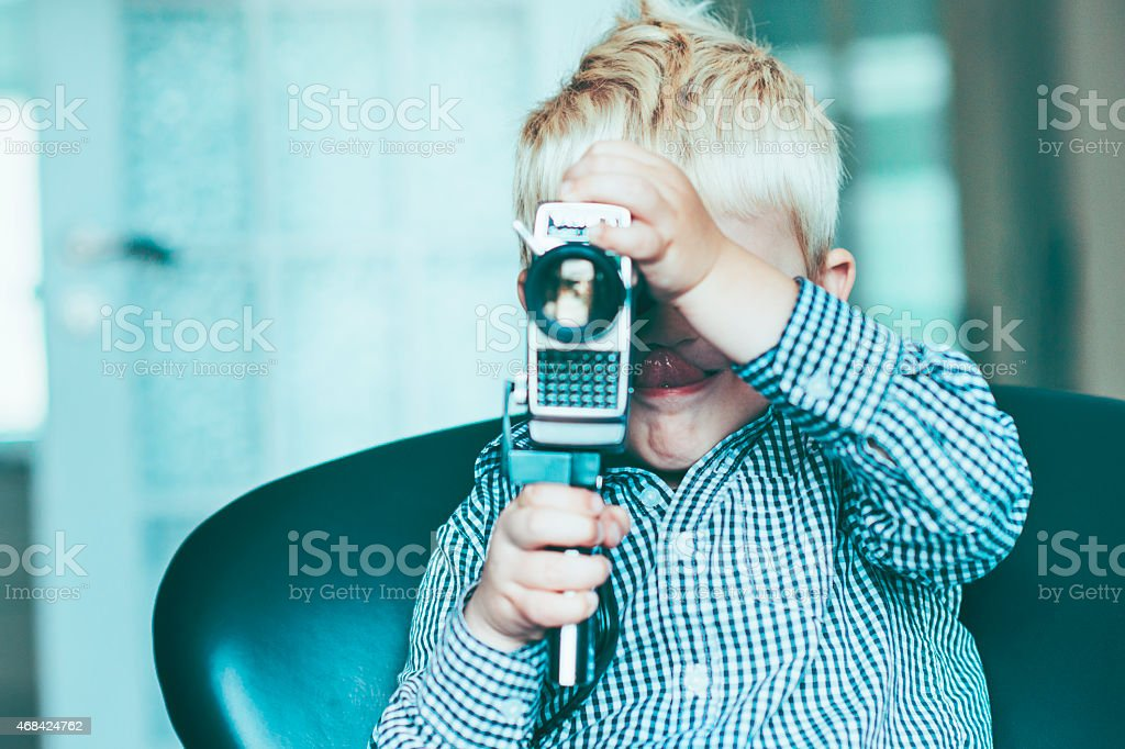 Child is creative with old video camera and makes movie stock photo
