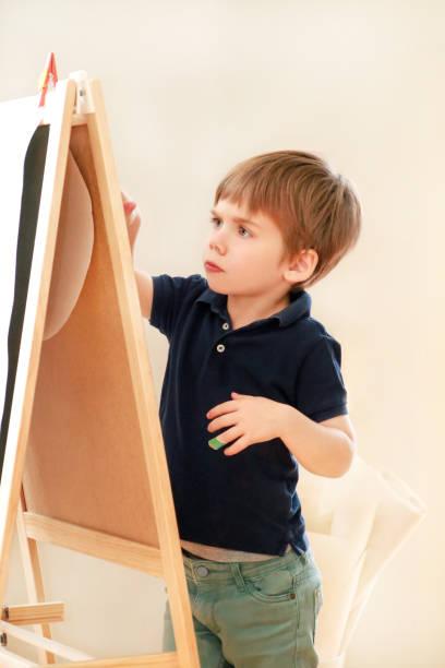 A criança está desenhando e pintando com pena de feltro no papel da armação de madeira do artista da placa de desenho para miúdos e crianças em casa. Infância. O rapaz pequeno bonito, miúdo desenha o lápis e marcadores coloridos no pré-escolar. - foto de acervo