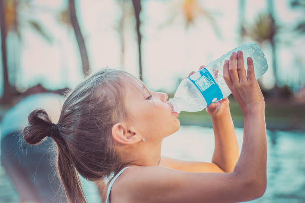 a child is drinking clean water from a bottle. hot summer day. - drinking water stock photos and pictures
