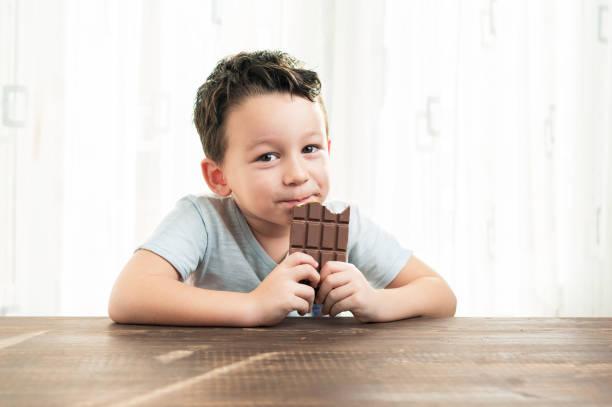 kind isst schokolade. - kinderschokolade stock-fotos und bilder
