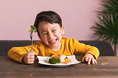 Child is eating vegetables. He is very happy.