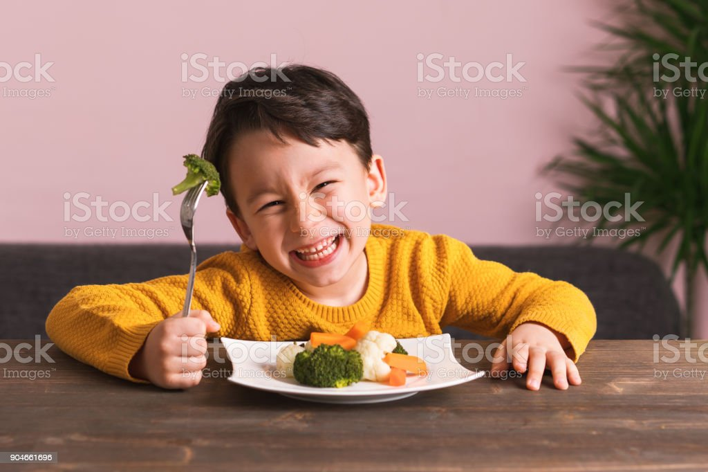 Child is eating vegetables. stock photo