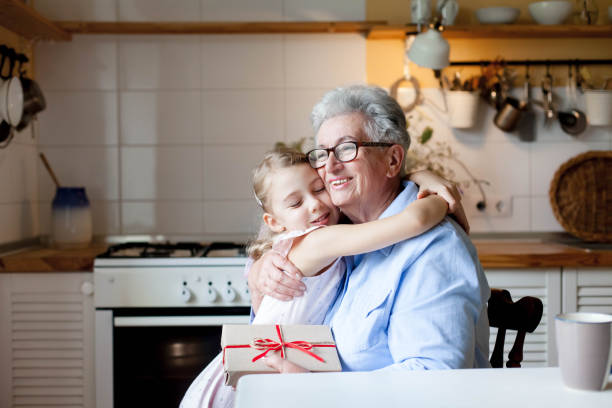Child is giving gift box to grandmother. Kid and senior woman are hugging in cozy home stock photo