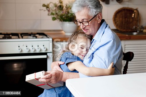 494086690istockphoto Child is giving gift box to grandmother. Kid and senior woman are hugging in cozy home 1188064464