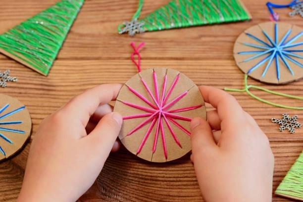 kind ist einen weihnachts-ball in den händen hält. kind zeigt eine weihnachtskugel. einfaches recycling-kunsthandwerk und aktivitäten für kinder. christbaumschmuck auf einem holztisch - bastelkarton stock-fotos und bilder