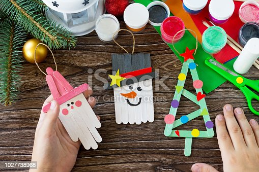 istock A child is holding Christmas decoration or Christmas gift wooden sticks. Handmade. Project of children's creativity, handicrafts, crafts for kids. 1027738968