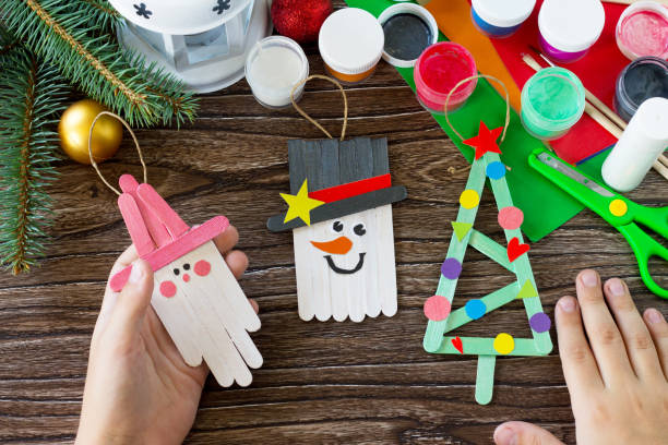 A child is holding Christmas decoration or Christmas gift wooden sticks. Handmade. Project of children's creativity, handicrafts, crafts for kids. stock photo