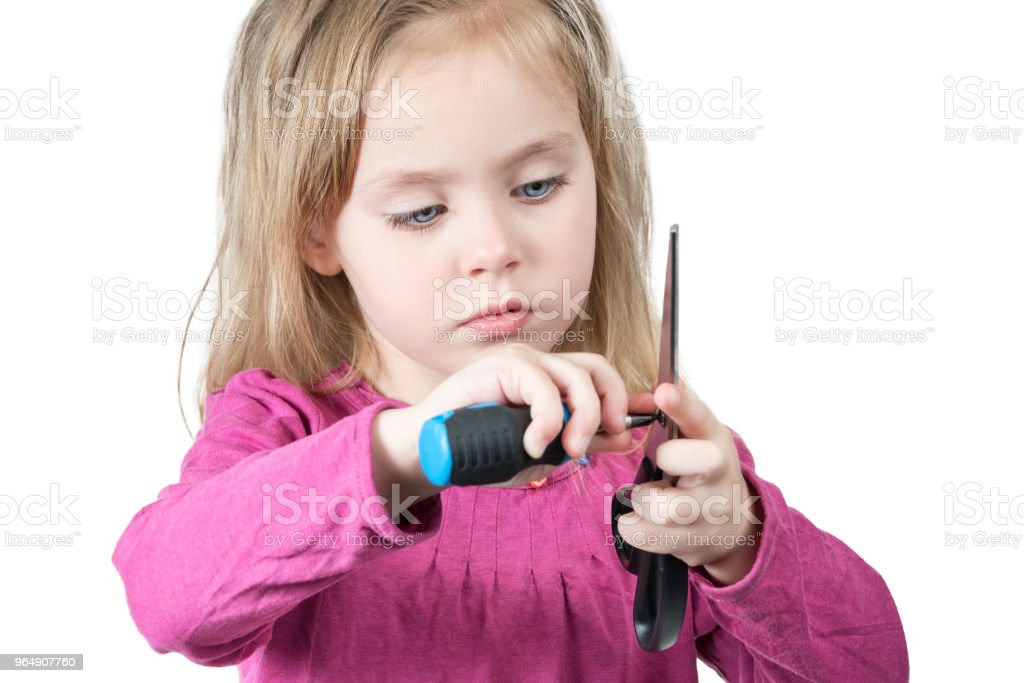 Child is holding scissors and a screwdriver royalty-free stock photo