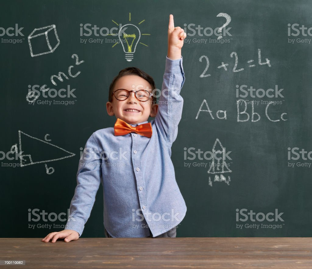 Child is in front of chalkboard and raising hand