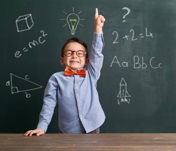 child is in front of chalkboard and raising hand - genius stock photos and pictures
