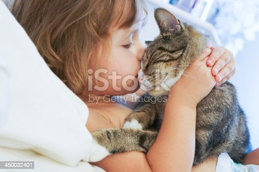 istock Child is kissing a cat 450032401
