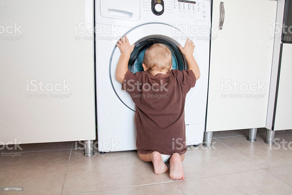 Kind, schaut in die Waschmaschine – Foto